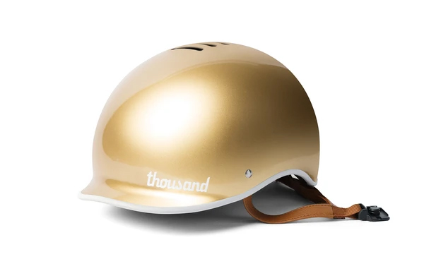Thousand bike helmet in gold on a white background